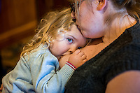 A mother comforts her daughter who is about two or three years old with a breastfeed at a sling meet held in the family restaurant and play area in a pub.<br /> Lancashire, England, UK<br /> <br /> Date Taken:<br /> 07-01-2015<br /> <br /> © Paul Carter / wdiip.co.uk