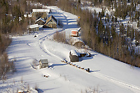 Aerial of Paul Gebhardt on Trail to Ophir Chkpt 2005 Iditarod passing Old Mining Cabins