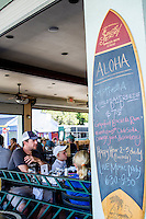 A family has a meal at Pineapples restaurant in downtown Hilo, Big Island of Hawai'i; a daily specials board shaped like a surfboard is on the right.
