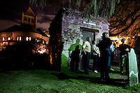A group of tourists take a night time ghost tour in a graveyard of Charleston, SC.