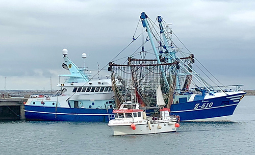 A local inshore fishing boat passes by the Belgian beam trawler moored alongside at Dun Laoghaire's Carlisle Pier
