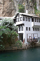 The house with stairs down to the river. The source of the Buna river and the house of the Whirling Dervishes, an old Muslim monastery, Blagaj. Federation Bosne i Hercegovine. Bosnia Herzegovina, Europe.