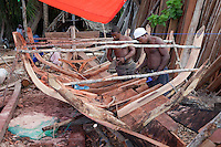 Nungwi, Zanzibar, Tanzania.  Dhow Construction.  Placing Fitting planks under the ribs that provide internal support and shape the hull.