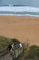 A lone surfer heads down stairs towards the ocean break along the Victorian coast, Australia