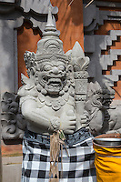Bali, Indonesia.  Hindu Temple Guardians Wrapped in Poleng Cloth, Symbolizing the Dualistic Nature of the Universe.  Pura Dalem Temple, Dlod Blungbang Village.