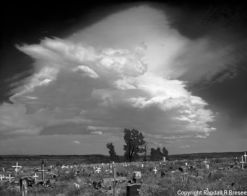 """""""Cloud Over Sacajawea"""" <br /> Wind River Reservation, Wyoming<br /> <br /> Sacajawea was a Shoshone Indian who provided valuable help to Lewis and Clark in the early 1800's. She is buried at the Indian Cemetery near Fort Washakie on the Wind River Reservation in Wyoming. I stopped to pay my respects to Sacajawea and recorded this black and white photograph of a beautiful cloud passing over the cemetery. Sacajawea's grave is marked by the largest monument in the cemetery and is located to the right of the photo's middle in front of the rightmost tree in the group of three trees of equal size."""