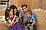 Couple in their twenties with two children, a 5 year old girl and a 7 month old baby boy, playing, singing song with hand motions