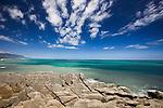 Pancake rocks with an aqua colored ocean behind, Punakaiki, New Zealand.