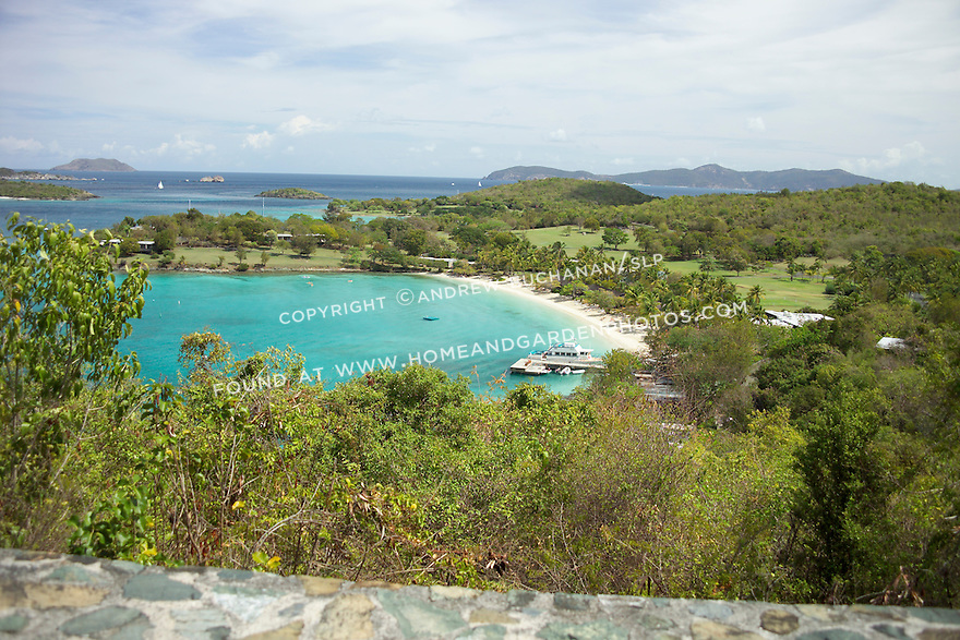 a ferry boat rests at the dock of Caneel Bay resort, as seen from the road above with blue green water, and other islands in the distance