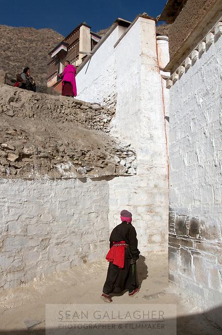 A Tibetan pilgrim walks around Labrang (Chinese Name - Xiahe) Monastery on the Qinghai-Tibetan Plateau. China.