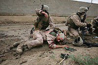Iraq: Karmah: October 31, 2006: Sgt Jesse E. Leach assists Lance CPL Juan Valdez of the 4th mobile assault platoon Weapons company 2nd battalion 8th Marines after he was shot by a sniper during a joined patrol with the Iraqi Army in Karmah, Anbar Province, Iraq. Valdez was shot through the arm and the right side but survived. To the right is Gunnery sgt Roger J Sands...