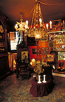 Clignancourt Flea Market shop with marble floor displays elegant furnishings, decorative items, mirror and paintings. Crystal chandeliers; candelabras and candlesticks on tables draped with red velvet; statuette; silver tea service, etc. Paris, France.