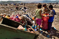 A Nicaraguan family members recollect plastic garbage for recycling in the garbage dump La Chureca, Managua, Nicaragua, 4 November 2004. La Chureca is the biggest garbage dump in Central America. Hundreds of trash recollectors search in tons of smouldering garbage mainly metals (copper, aluminium), others concentrate on glass which is cheap, but in bigger amount. The majority of the recyclers are families with children for whom recycling is a regular job. The children very often eat the food they find on the dump, none of them goes to school, they suffer from skin diseases, they have high levels of lead and DDT in blood.