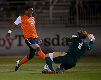 Patrick Wall (1) of Notre Dame slides to save the shot of Marcus Salandy -Defour (16) of Virginia during the ACC tournament semifinals at the Maryland SoccerPlex in Boyds, MD.  Virginia advanced to the finals after tying Notre Dame, 3-3, in overtime and then defeating them on penalty kicks.
