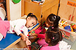 Education preschool 3-4 years old  pretend play group of three girls playing with medical kit one girl giving shot to patient