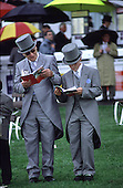 Father and son in front of the Queens Stand at Epsom Downs racecourse on Derby Day.
