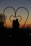 A sihouette of a couple embracing, framed in the back of a heart-shaped wire chair against the sunset from Olive Hill in East Hollywood, CA