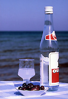 Greece. A drink and bottle of Ouzo, plus a plate of black olives on a table by the sea.