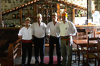 UNK UNK the owner of the restaurant in traditional clothing and Albanian hat, white with round top tied with an orange yellow cloth and the staff waiters of the restaurant. Tradita traditional restaurant, Shkodra. Albania, Balkan, Europe.
