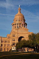 A bronze statue of a Texas Ranger stands in front of the State Capitol Building in Austin, Texas.