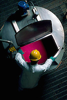Overhead shot of paper plant worker looking into vat of dye.