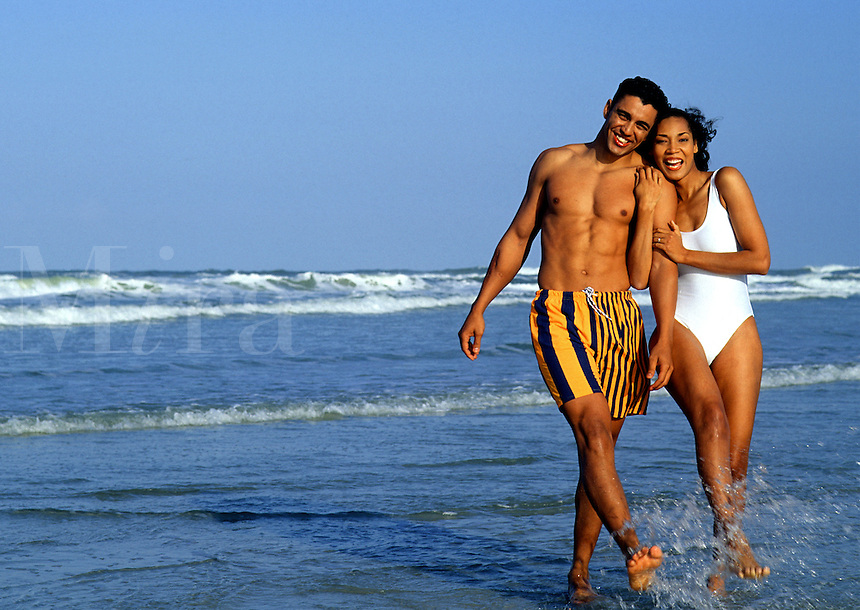 A smiling young African American couple takes an affectionate stroll in the surf.