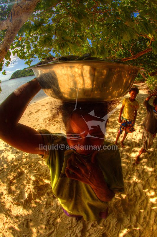 Woman with her children carrying a steel bowl full of sardines at Bagaman Island in the  Louisiade Archipelago..The Louisiade Archipelago is a string of ten larger volcanic islands frequently fringed by coral reefs, and 90 smaller coral islands located 200 km southeast of New Guinea, stretching over more than 160 km and spread over an ocean area of 26,000 km  between the Solomon Sea to the north and the Coral Sea to the south. The aggregate land area of the islands is about 1,790 kmu178  (690 square miles), with Vanatinai (formerly Sudest or Tagula as named by European claimants on Western maps) being the largest..Sideia Island and Basilaki Island lie closest to New Guinea, while Misima, Vanatinai, and Rossel islands lie further east..The archipelago is divided into the Local Level Government (LLG) areas Louisiade Rural (western part, with Misima), and Yaleyamba (western part, with Rossell and Tagula islands. The LLG areas are part of Samarai-Murua District district of Milne Bay. The seat of the Louisiade Rural LLG is Bwagaoia on Misima Island, the population center of the archipelago. .The Louisiade Archipalego is part of the Milne Bay province of Papua New Guinea..It lies between approximately 10 degrees south and 11.5 degrees south, and 151 degrees east and 154 degrees east. It is an area of Islands, reefs and cays some 200 nm long and 50 nm wide, stretching from the south east tip of mainland Papua New Guinea in a east south east direction..Bagaman Island in the  Louisiade Archipelago..The Louisiade Archipelago is a string of ten larger volcanic islands frequently fringed by coral reefs, and 90 smaller coral islands located 200 km southeast of New Guinea, stretching over more than 160 km and spread over an ocean area of 26,000 km  between the Solomon Sea to the north and the Coral Sea to the south. The aggregate land area of the islands is about 1,790 kmu178  (690 square miles), with Vanatinai (formerly Sudest or Tagula as named by European claimants on Western