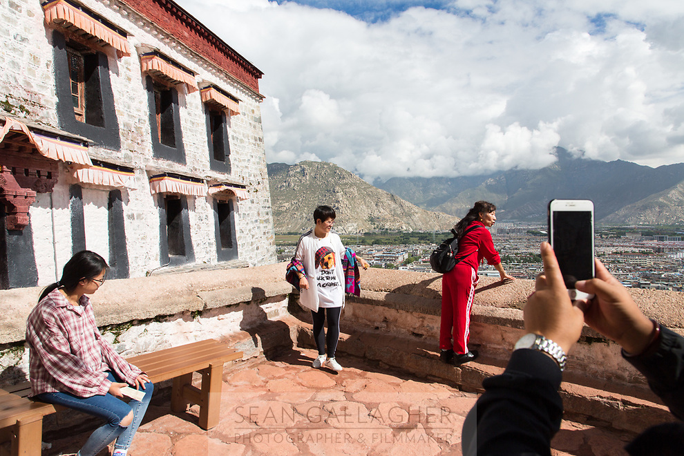 Tourists take in the view from the Potala Palace in Lhasa. One of the spiritual centers of Tibet, it is also the number one tourist sight in the city leading to thousands of tourists and pilgrims visiting each day. Most walk clockwise around the palace, pausing to pray, or take pictures, of the sacred structure before them.