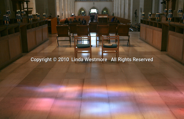 """Light coming through the stained glass window, """"Service"""" by Mark Angus lands on the floor.  Looking away from the High Altar of Guildford Cathedral."""