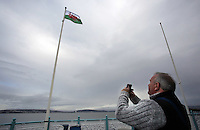 Grant Eden takes a picture of a Wales flag in the shape of a red lobster instead of a red dragon is raised outside Mumbles Pier, to raise awareness for Skin Care Cymru, in Wales, UK. Tuesday 28 February 2017
