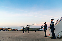 Military personnel salute the arrival of Marine One carrying President Donald J. Trump at Joint Base Andrews, Md. Tuesday, Oct. 20, 2020, and are escorted to Air Force One by U.S. Air Force personnel. (Official White House Photo by Tia Dufour)