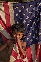 Bangladesh, Cox's Bazar. Kutupalong Rohingya Refugee Camp. The Rohingya, a Muslim ethnic group  denied citizenship in Burma/Myanmar have escaped persecution from Burmese militants in their country. There are up to 500,000 refugees and migrants living in makeshift camps in Cox's Bazar. Boy standing in front of American flag door.