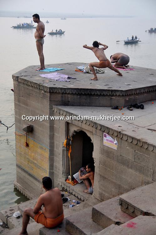 Indian men in their daily chore at a ghat in Varanasi, Uttar Pradesh, India.