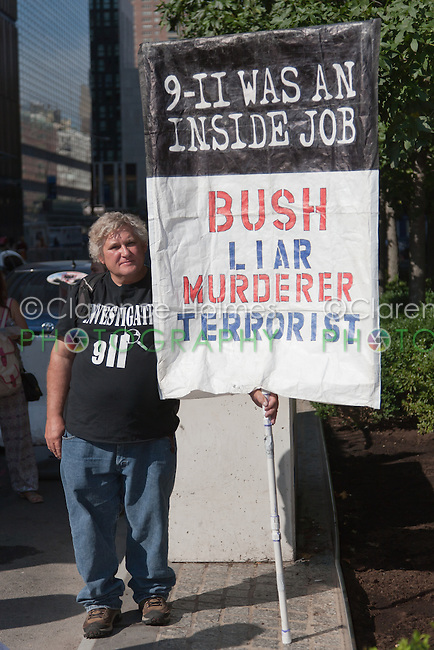 A protester holds a sign stating (9-11 was an inside job.  Bush/Liar/Murderer/Terrorist.
