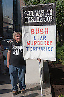 A protester holds a sign stating (9-11 was an inside job.  Bush/Liar/Murderer/Terrorist.