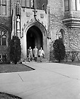 GPHR 45/0033:  Three male student exiting the western door of the Law School Building, c1950s..Image from the University of Notre Dame Archives.