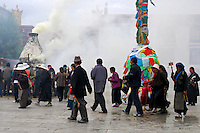 Tibetan Buddhist pilgrims circumambulate the Barkhor prayer circuit around a prayer flag pole and smoky incense burner in front of the Jokhang Temple, during Saga Dawa festival,  Lhasa, Tibet.