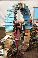 Wednesday 28 May 2014, Hay on Wye, UK<br /> Pictured: A little girl playing by a sculpture made out of used books<br /> Re: The Hay Festival, Hay on Wye, Powys, Wales UK.