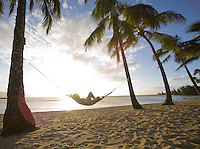 Man relaxing in a hammock under a palm tree in the sun, Haleiwa Beach park, North Shore Oahu