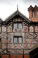 Detail of the plaster sgraffito decorations on one of the timber framed wings, including a swan and coats of arms