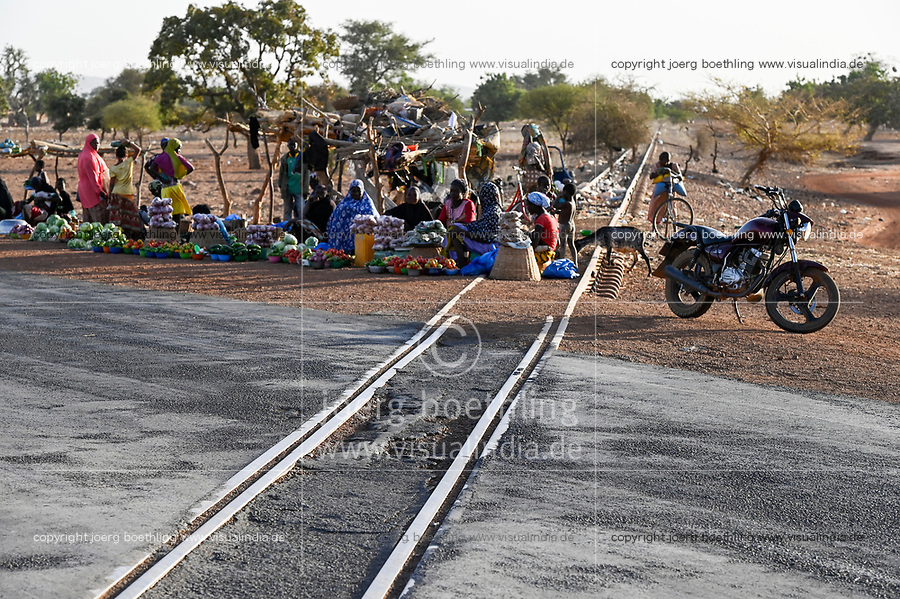 BURKINA FASO, Kaya, abandoned railway line to the Manganese ore mines in Tambao, built during Thomas Sankara time, people selling vegetable at road rail crossing / von Sankara gebaute Eisenbahnlinie zu den Mangan Lagerstätten in Tambao