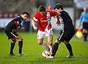 Ayr Utd's Adam Hunter gets past Pars' Faissal El Bakhtaoui and Ross Forbes.