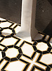 Tristan, a waterjet stone mosaic shown in polished Nero Marquina and honed Calacatta Monet with brushed Brass, is part of The Studio Line of Ready to Ship mosaics by New Ravenna.