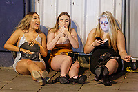 Pictured: Three female revellers sit on the pavement in Wind Street, Swansea. Monday 31 December 2018 and Tuesday 01 January 2019<br /> Re: New Year revellers in Wind Street, Swansea, Wales, UK