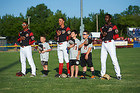 """Batavia Muckdogs players including Jhonny Santos (32), Corey Bird (12) and Isaiah White (18) stand with the """"Stars of the Game"""" for the national anthem before a game against the State College Spikes on June 24, 2016 at Dwyer Stadium in Batavia, New York.  State College defeated Batavia 10-3.  (Mike Janes/Four Seam Images)"""