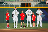 (L-R) Slade Heathcott (26), Adam Engel (12), and Jason Coats (17) are joined on the field by members of the Lake Norman Copperheads for the National Anthem prior to the game against the Scranton/Wilkes-Barre RailRiders at BB&T BallPark on July 20, 2016 in Charlotte, North Carolina.  The RailRiders defeated the Knights 14-2.  (Brian Westerholt/Four Seam Images)