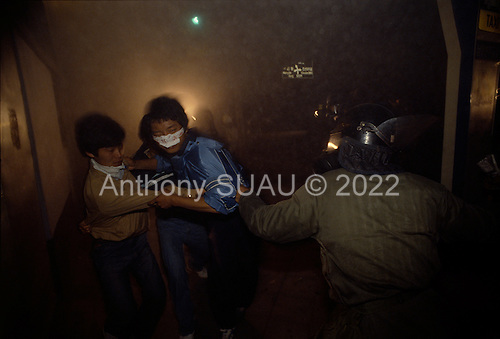 """Kwanju, South Korea.May 1987..Plain-clothed policeman acts in unison with riot police to arrest a student demonstrator...After two decades of building an economic miracle, in the summer of 1987 tens of thousands of frustrated South Korean students took to the streets demanding democratic reform. """"People Power"""" Korean-style saw Koreans from all social spectrums join in the protests...With the Olympics to be held in South Korea in 1988, President Chun Doo Hwan decided on no political reforms and to choose the ruling party chairman, Roh Tae Woo, as his heir. The protests multiplied and after 3 weeks Chun conceded releasing oppositionist Kim Dae Jung from his 55th house arrest and shaking hands with opposition leader Kim Young Sam. Days later he endorsed presidential elections and an amnesty for nearly 3,000 political prisoners. It marked the first genuine initiative of democratic reform in South Korea and the people had their victory."""