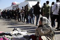 Pictured: A migrant woman sitting on the ground hides her face infront of a long queue Thursday 03 March 2016<br /> Re: Migrants have been gathering at the port of Piraeus, near Athens, Greece