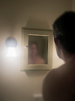 Man confronts his murky image in the mirror.
