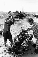 Iraq. Baghdad. Waste of the war. Two men dismantle the engine of  a destroyed iraqi tank shot by air strikes attacks from the coalition forces (american army). They will then sell the spare parts as recycled pieces abroad.  © 2003 Didier Ruef